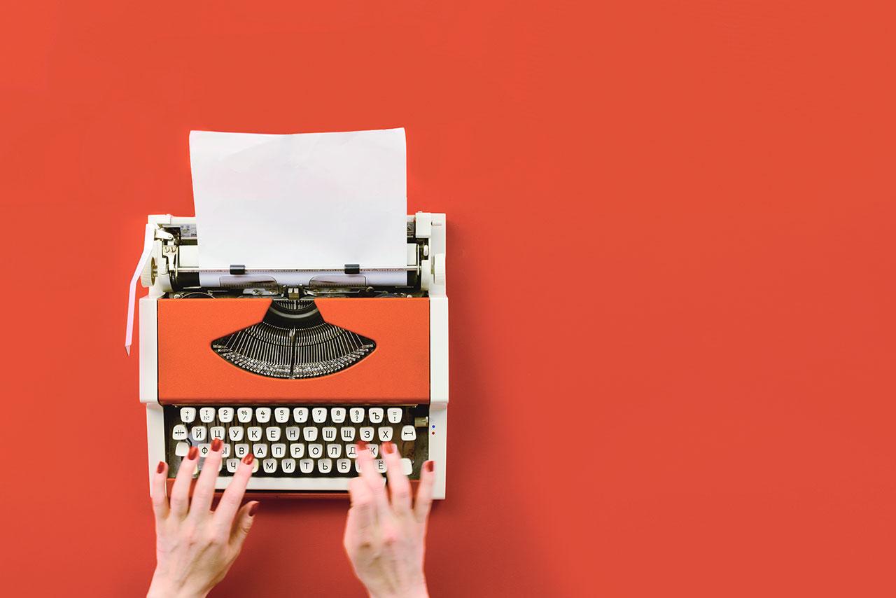 mãos digitando uma maquina de escrever sobre fundo laranja