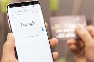 mão segurando smartphone google shopping cartão de crédito