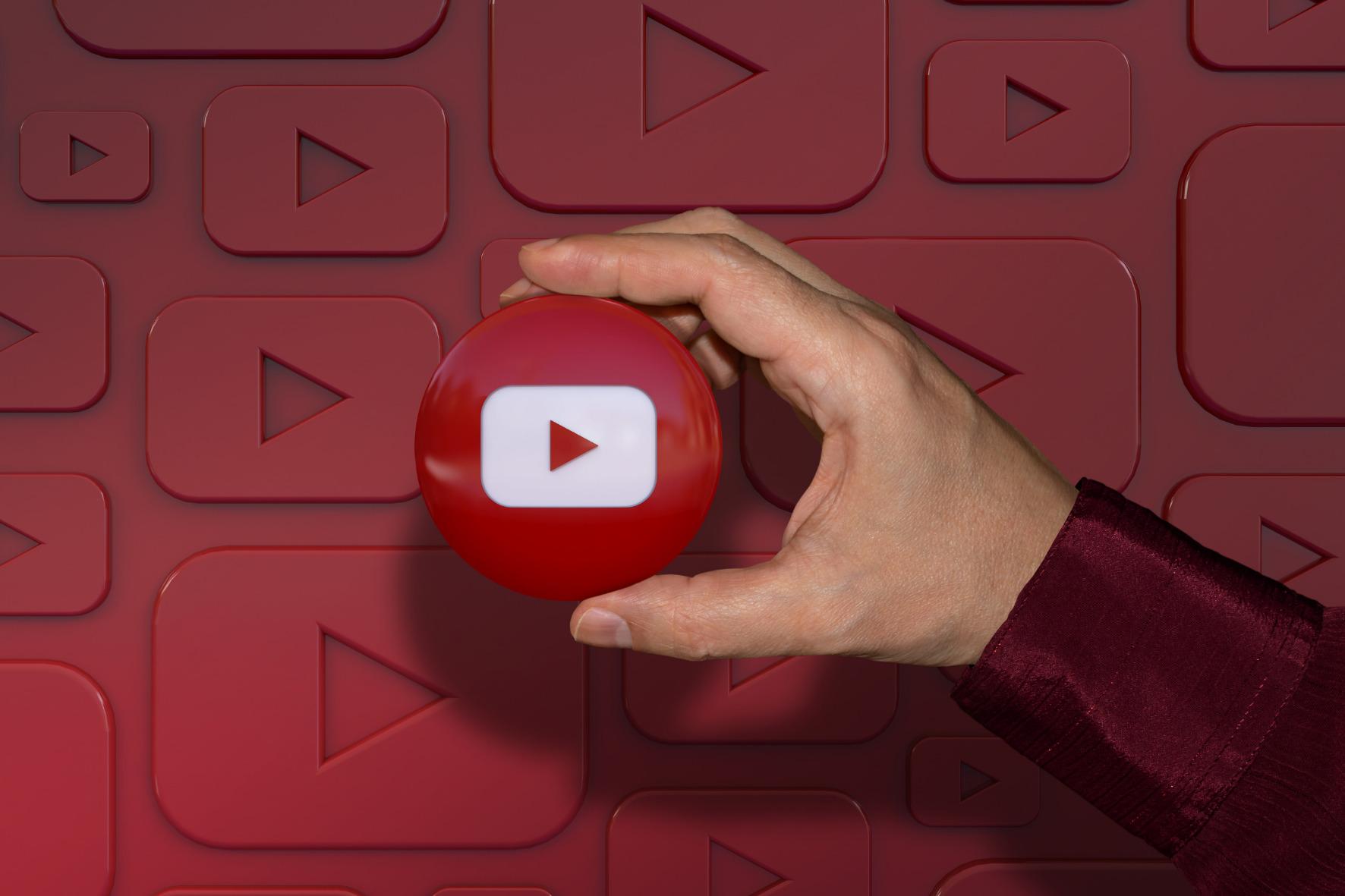 canal no youtube mão segurando logotipo fundo vermelho